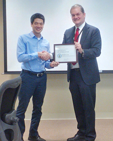 Dr. Kevin Fu receives a certificate for his service for ISPAB from Chuck Romine, NIST's ITL Director.